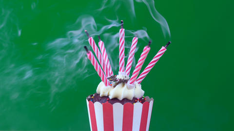 4k Green screen red and white striped cupcake, blowing out candles Footage