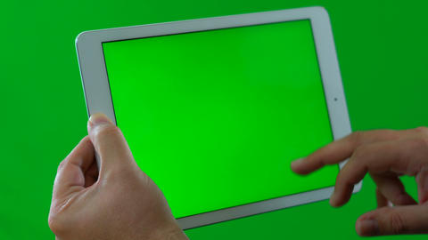 Man using and typing on tablet device against green screen, to the side, close Live Action