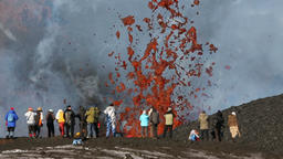 Travelers take pictures fountain of flying red hot lava, erupting from volcano ビデオ