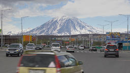 Automobiles drive along city road on background of active volcano Footage