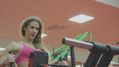 Very beautiful female trainer trains on a fitness machine in a fitness club Live Action