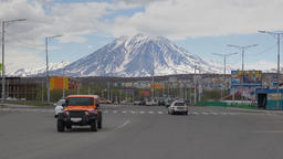 Automobiles drive along city road on background of volcano. Time lapse Footage