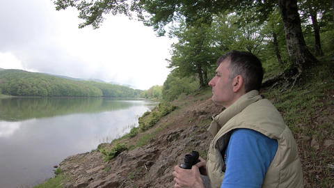 Man looks through binoculars at distance while sitting at scenic river bank on Footage