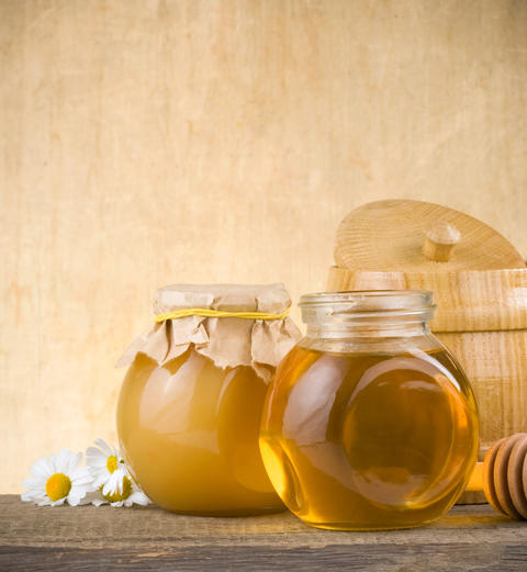 glass jar of honey and stick Photo