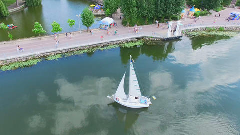 Aerial View . Beautiful top view of the lake and city park. Yacht on the blue Footage