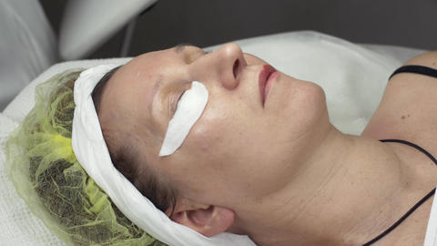 Adult woman lie in beauty saloon with cotton pad under eyelashes. Permanent dye Footage