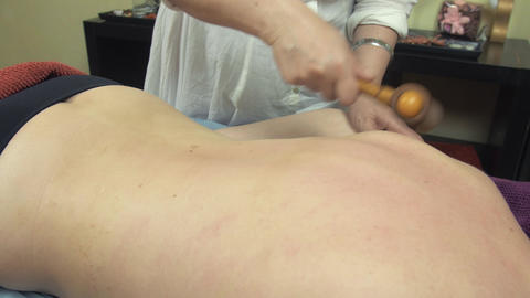 Masseuse make medical massage of backbone by wooden massage roller to woman Footage