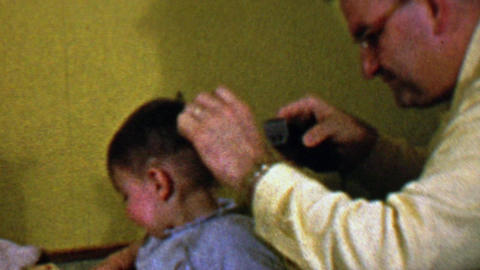 1957: Dad cuts bold baby hair with electric buzzers shaves head Footage