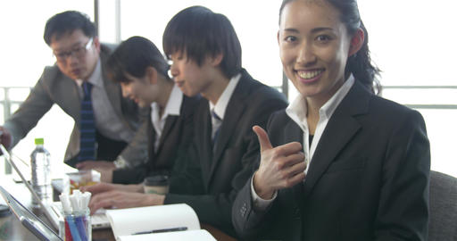 Confident young Japanese business women gives thumbs up after answering call ライブ動画