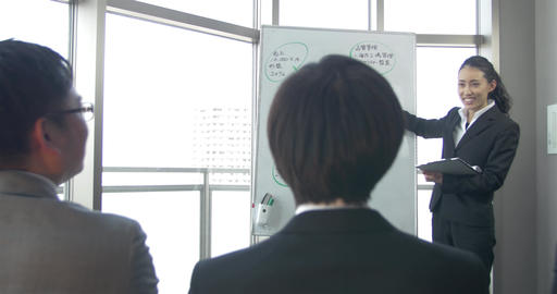 Energetic Young Japanese women presents to her work colleagues Footage