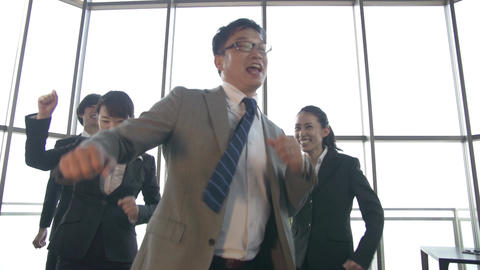Japanese boss and his team celebrate by dancing in the office slow motion Footage