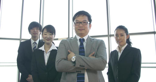 Japanese boss stands in powerful pose with his small company team Footage