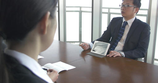 Japanese boss talking to subordinates about weekly reports Footage