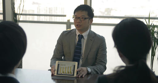 Japanese business man explains numbers to job applicants Footage