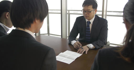 Japanese businessman talks to job applicants about contracts Footage