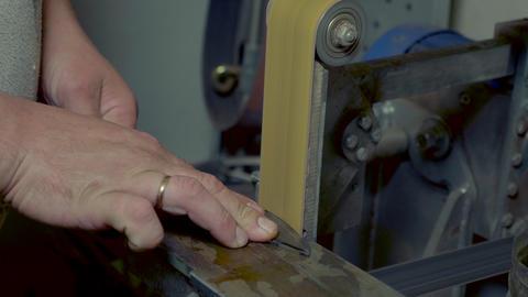 Diy man grinding metal knife with sparks on grinder in workshop Footage