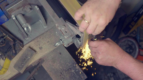 Workman making knife blade with sparks on abrasive machine, do it yourself, high Footage