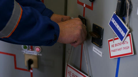 electrician hangs up warning sign on switchboard door Live Action