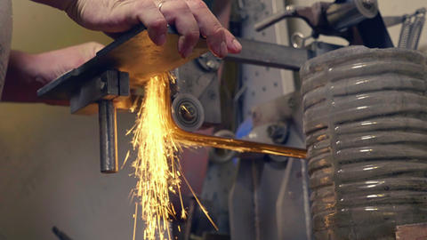 Man grinding handmade metal knife on abrasive machine with sparks, bottom view Footage