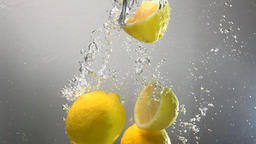 Whole lemon drops under water. Isolated Footage