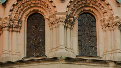 Stained-glass windows of arched form of old cathedral, dome with golden cross Footage