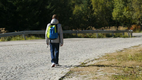 Young man going down empty road in mountains looking around, active tourism Footage