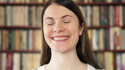 Female college student smiling in library. First day of school. Bookcase ビデオ