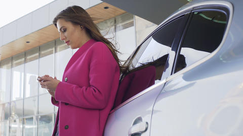 Pretty lady in pink coat standing near automobile and scrolling on smartphone Footage