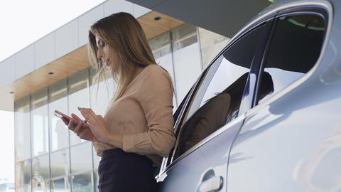 Nice businesslady chatting with client on smartphone, standing near automobile Footage