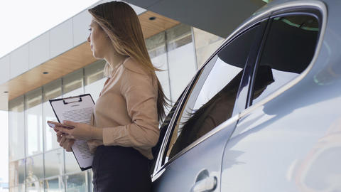 Female insurance broker holding contract and waiting for client near automobile Footage