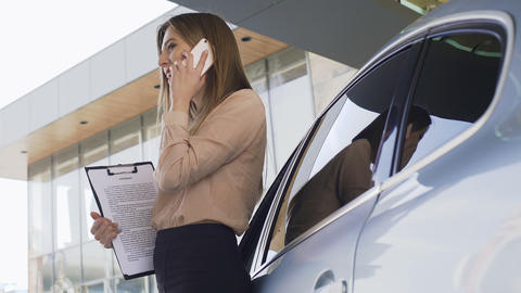 Lady broker with contract talking with client on smartphone, standing near car Footage