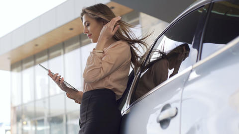 Beautiful independent woman browsing on tablet near automobile, business Footage