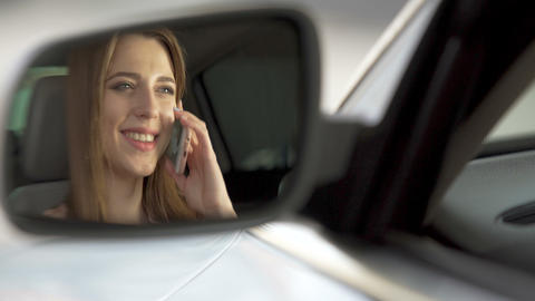 Cheerful woman sitting in automobile and talking on smartphone with parents Footage