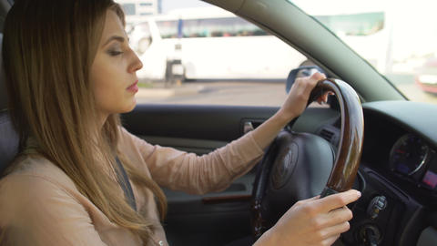 Self-confident business lady driving car, intensive urban traffic, big city life Live Action