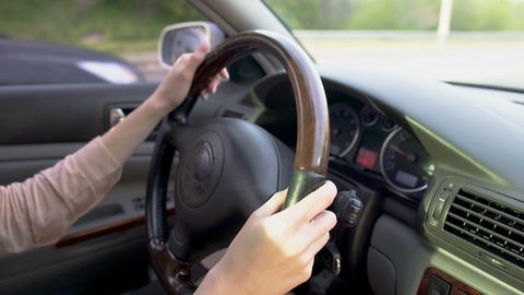 Attentive woman driving automobile. Close-up of hands turning steering wheel Footage