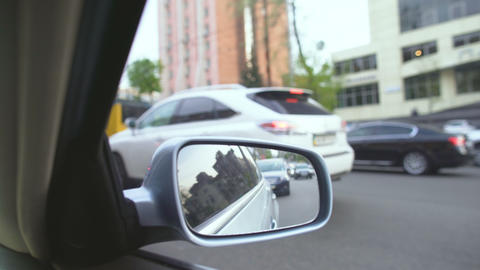 View from moving automobile, reflection in rearview mirror. Traffic jam in city Live Action