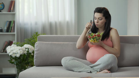 Eternally hungry pregnant girl eating salad, saturating body with vitamins Footage