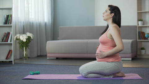 Pregnant lady doing breathing and relaxation exercises, preparing for childbirth Footage