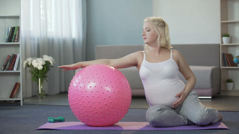 Pregnant girl doing exercises at home, removing tension from her tired body Footage