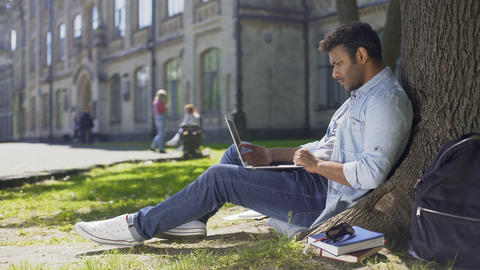 College student sitting under tree, using laptop looking worried, upsetting news Footage