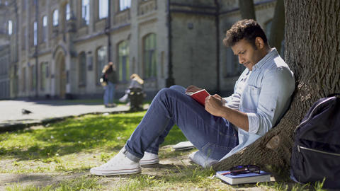 Multiracial young guy sitting under tree, reading interesting book, bookworm Footage
