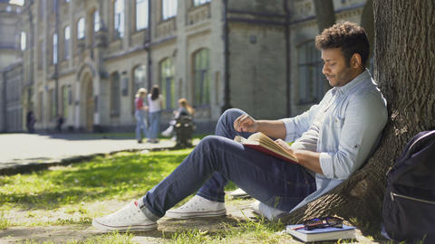 Multinational guy sitting under tree, reading book looking around, leisure time Footage