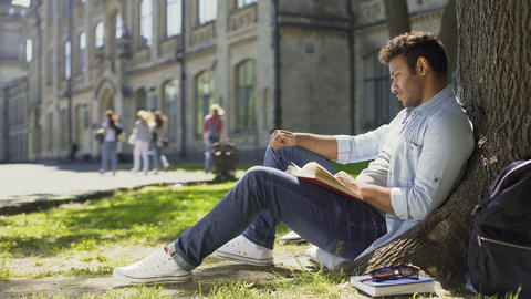 Young male sitting under tree with book looking around, having pleasant thoughts Footage