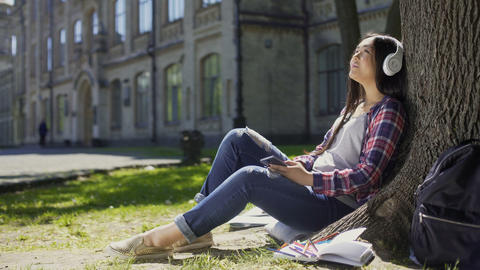Female student sitting on grass, leaning against tree, listening to music, relax Footage