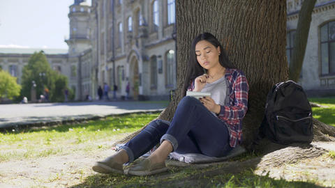 Multinational young woman taking notes in notebook sitting under tree, essay Footage