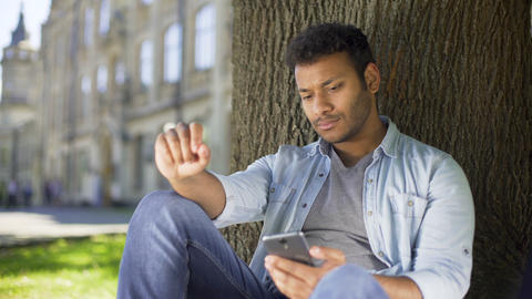 College student reading newsfeed on phone, getting disappointed with news, upset Footage