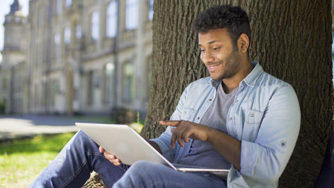 Mixed-race young man chatting on laptop, sitting under tree, dating website Live Action