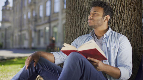 Young man sitting under tree reading book and thinking, literature, fiction Footage