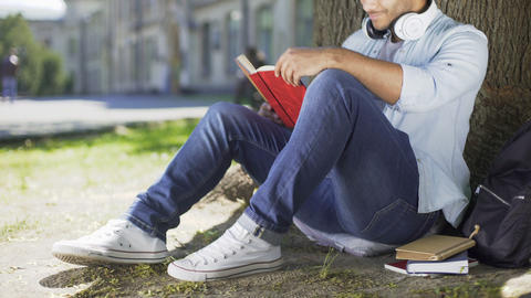 Multiracial male sitting under tree and reading, smiling and closing book, happy Footage
