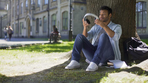 Young man putting headphones, listening to music sitting under tree, admiration Footage